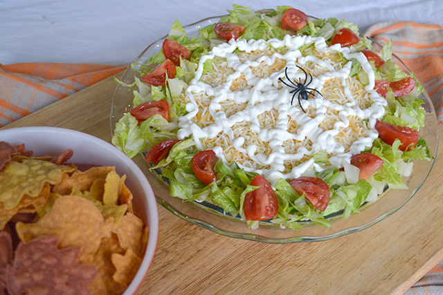 Halloween theme taco dip with a sider web on top made of sour cream next to a bowl of tortilla chips
