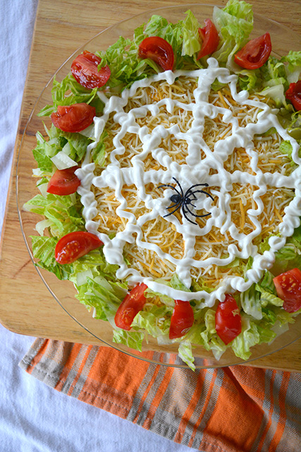 Seven layer taco dip for Halloween with a sour cream spider web on top of the cheese layer