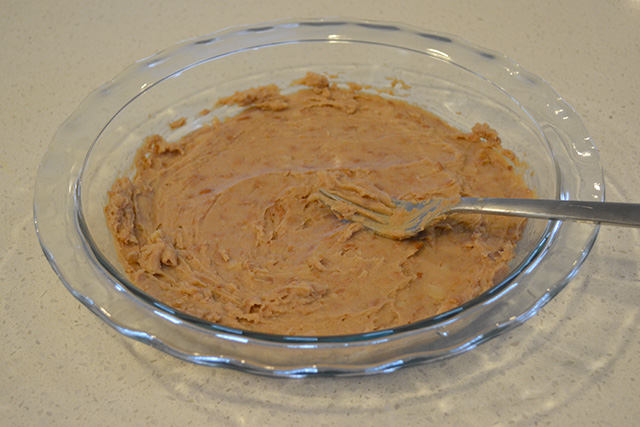 refried beans smoother out in a pie plate for 7 layer dip