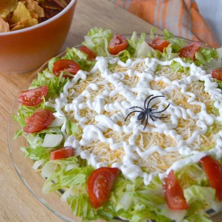 Halloween themed 7 layer taco dip with a spider web on top made with sour cream topped with plastic spider
