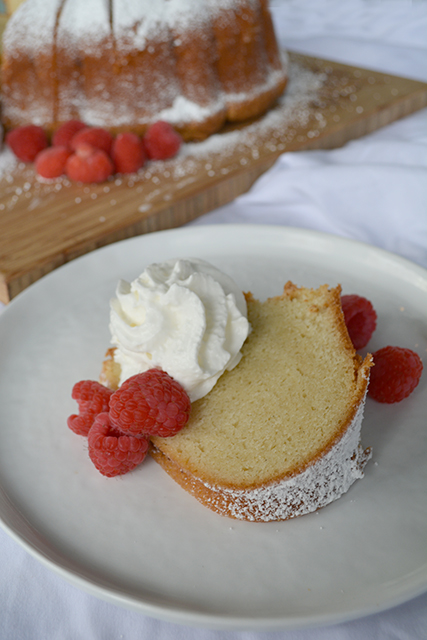 slice of sour cream pound cake on a white plate with the rest of the bundt next to it on a wooden cutting board