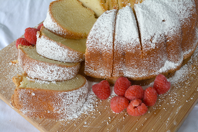 Sliced Sour Cream Pound Cake on a wooden cutting board dusted with powdered sugar accented with raspberries