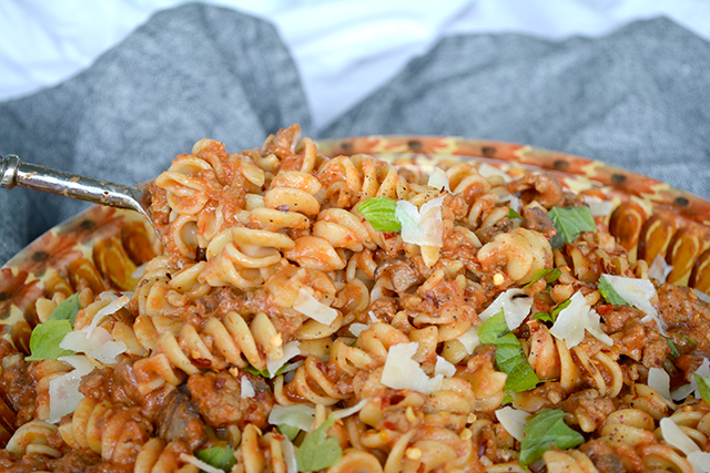 close up of hearty mushroom and sausage pasta in a large serving bowl