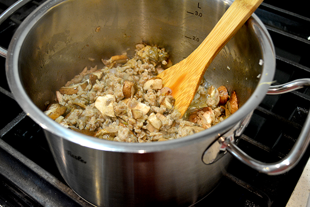 wooden spoon mixing mushrooms and Italian sausage in a large pot