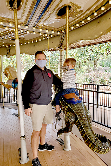 little boy with father on carousel at Jacksonville Zoo
