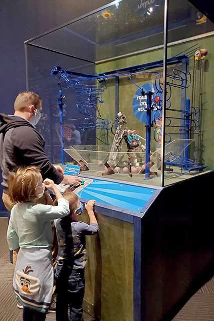 family playing claw and ball game at MOSH exhibit