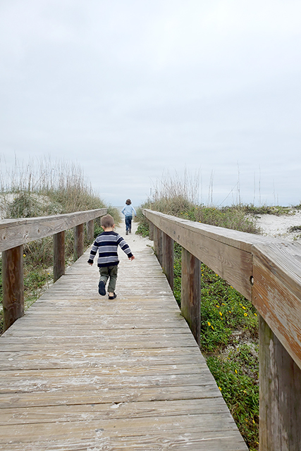 little girl leading boy on entrance to Jacksonville beach