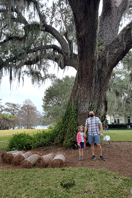 man holding hands with his daughter in front of giant spanish moss covered oak tree