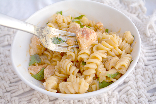 fork picking up rotini pasta with diced chicken in a creamy sauce that was cooked in an Instant Pot