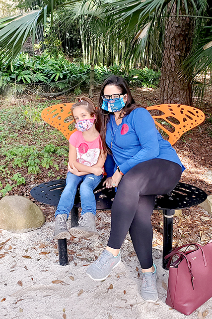 women at young girl taking picture together on butterfly bench at Jacksonville Zoo