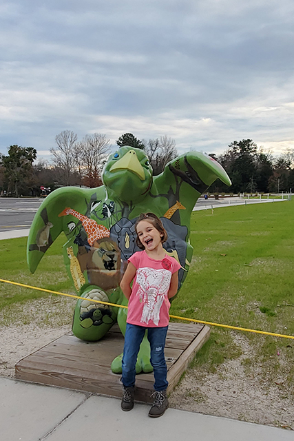 Little Girl standing in front of painted turtle sculpture