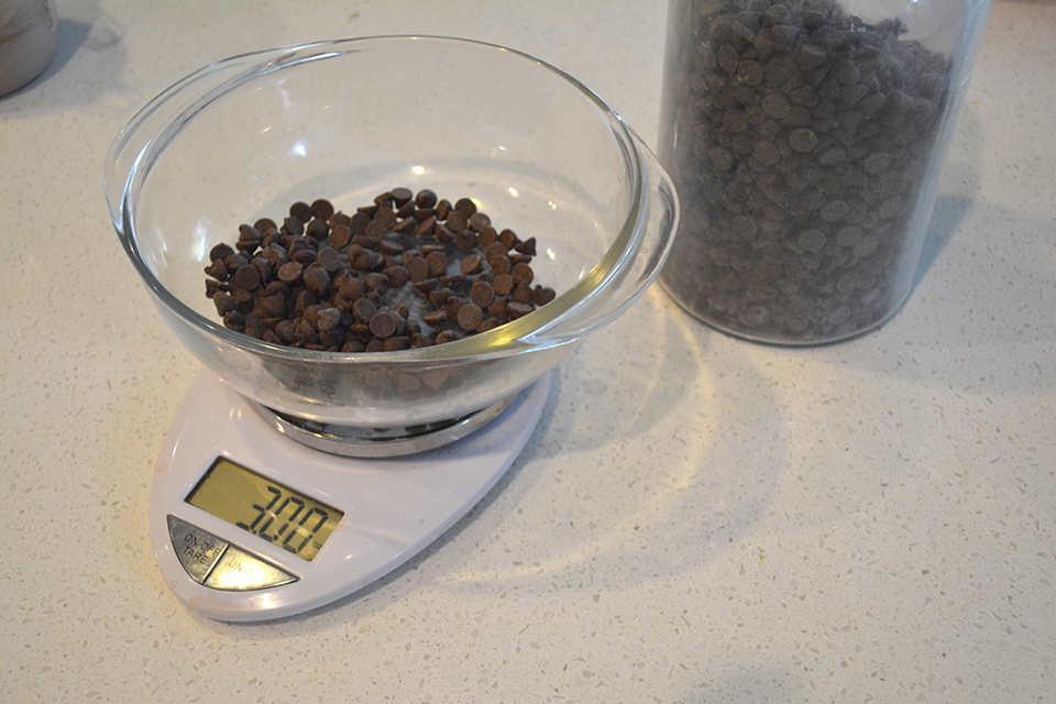 glass bowl of chocolate chips on a kitchen scale