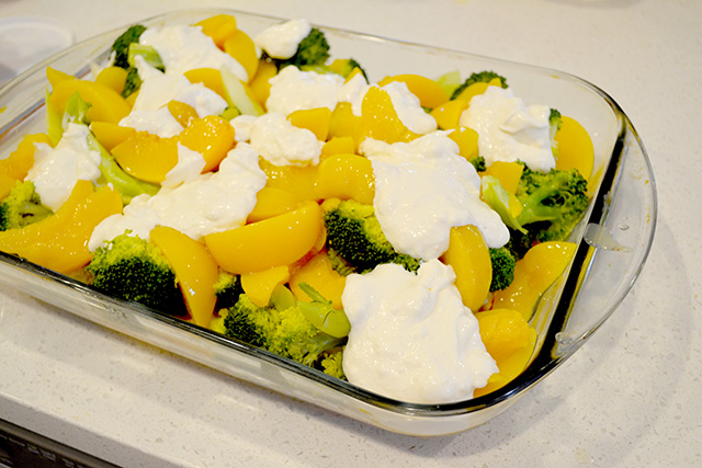 cheesy sour cream sauce dolloped on broccoli and peaches for Chicken Broccoli Peach Bake