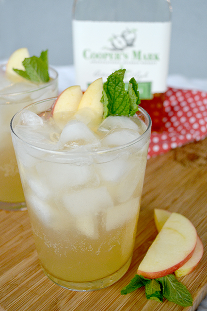 Close up on Apple Whiskey Lemonade Spritzer on a cutting board in front of a bottle of apple flavored whiskey.