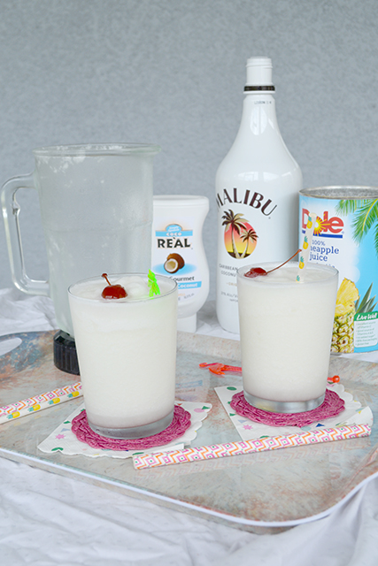 2 glasses of Frozen Pina Coladas in front of ingredients and blender.