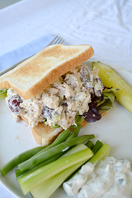 Chicken Salad Sandwich on toasted white bread on white plats with vegetables next to it.