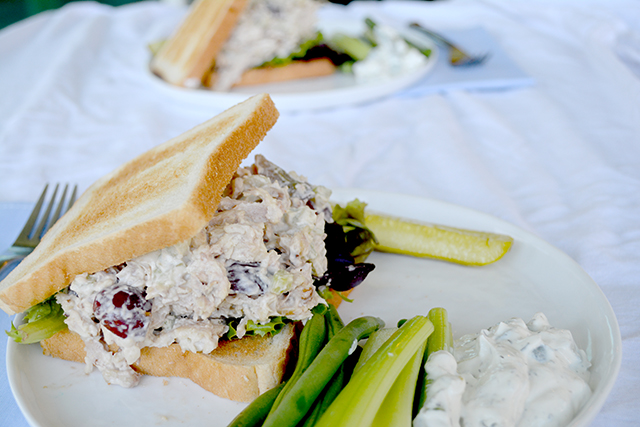 chicken salad sandwich on toasted white bread on a white plate next to celery sticks.