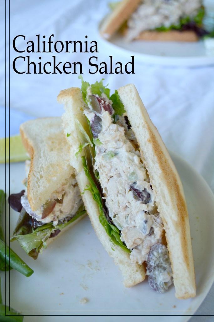 chicken salad sandwich cut in half on white plate.
