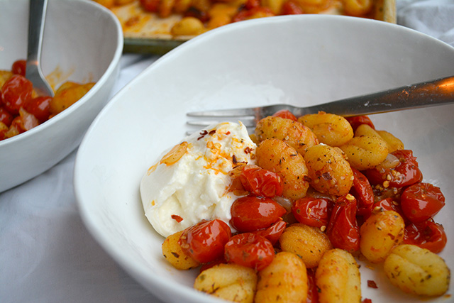 Close up of bowl of gnocchi with fresh tomato sauce and side of burrata.