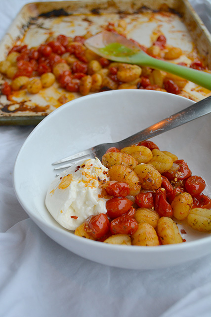 Bowl of Easy Sheet Pan Gnocchi in front of sheet pan with rubber spatula on it..