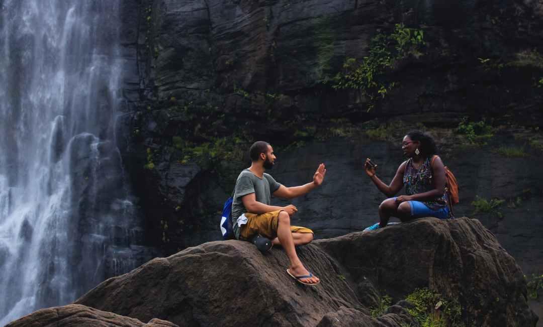 man and woman talking near waterfalls