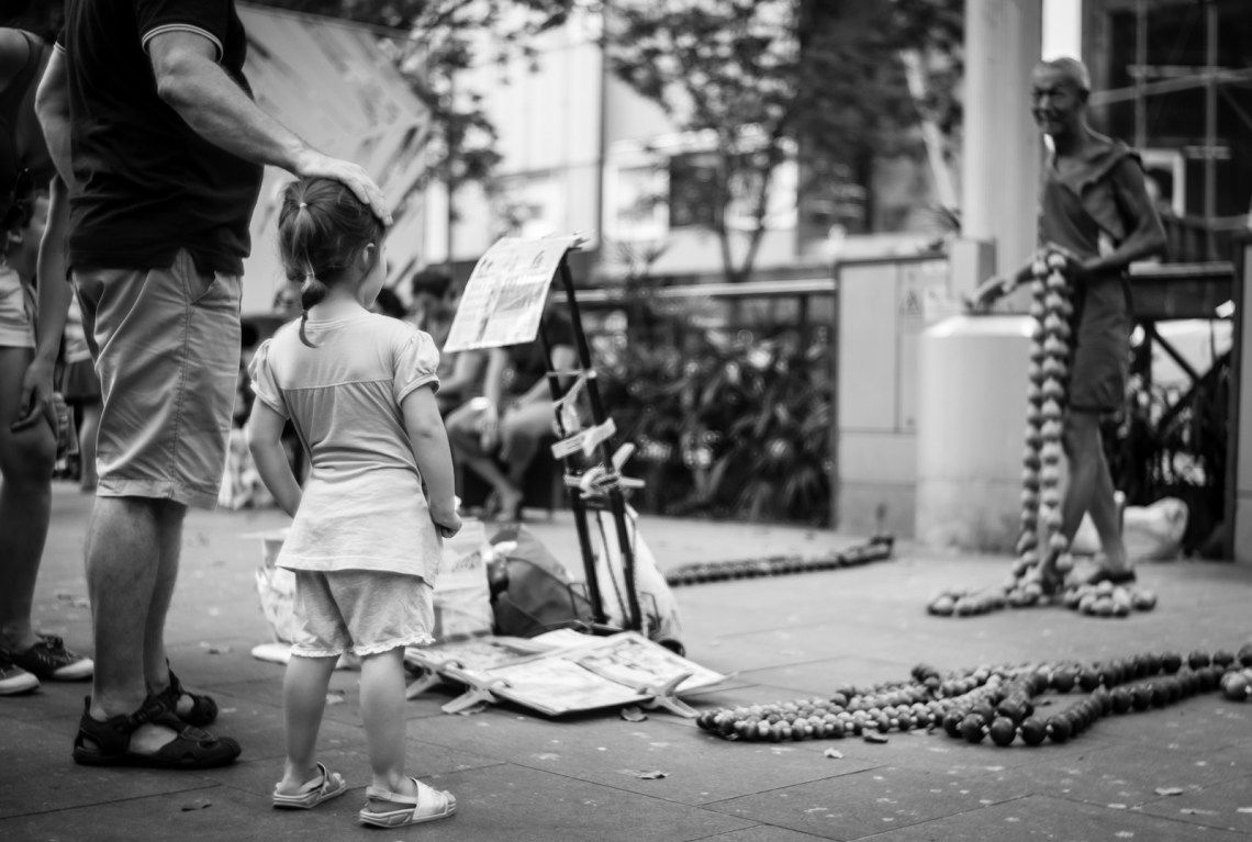 Street photography - Man patting his daughter's head as she watches the street performer