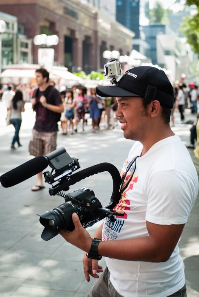 A cameraman wearing a cap