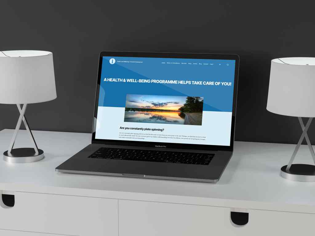 The JL Consultancy website is displayed on a Macbook Pro. The laptop is on a white desk with a white and silver lamp on either side of it. The desk is against a grey wall.