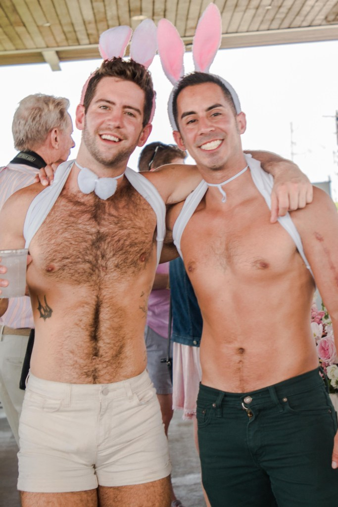 23 shirtless hunk wearing bunny ears and over-the-top Easter bonnets