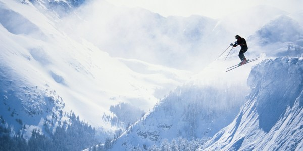 Skiier leaping from ledge, Taos Ski Valley, New Mexico, USA