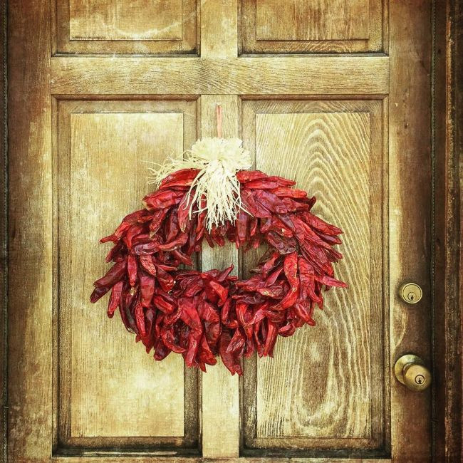 A New Mexico Red Chile Wreath Hung on a Door, at a Santa Fe, New Mexico, residence. / Photo credit by Instagram user @kathleenclemons