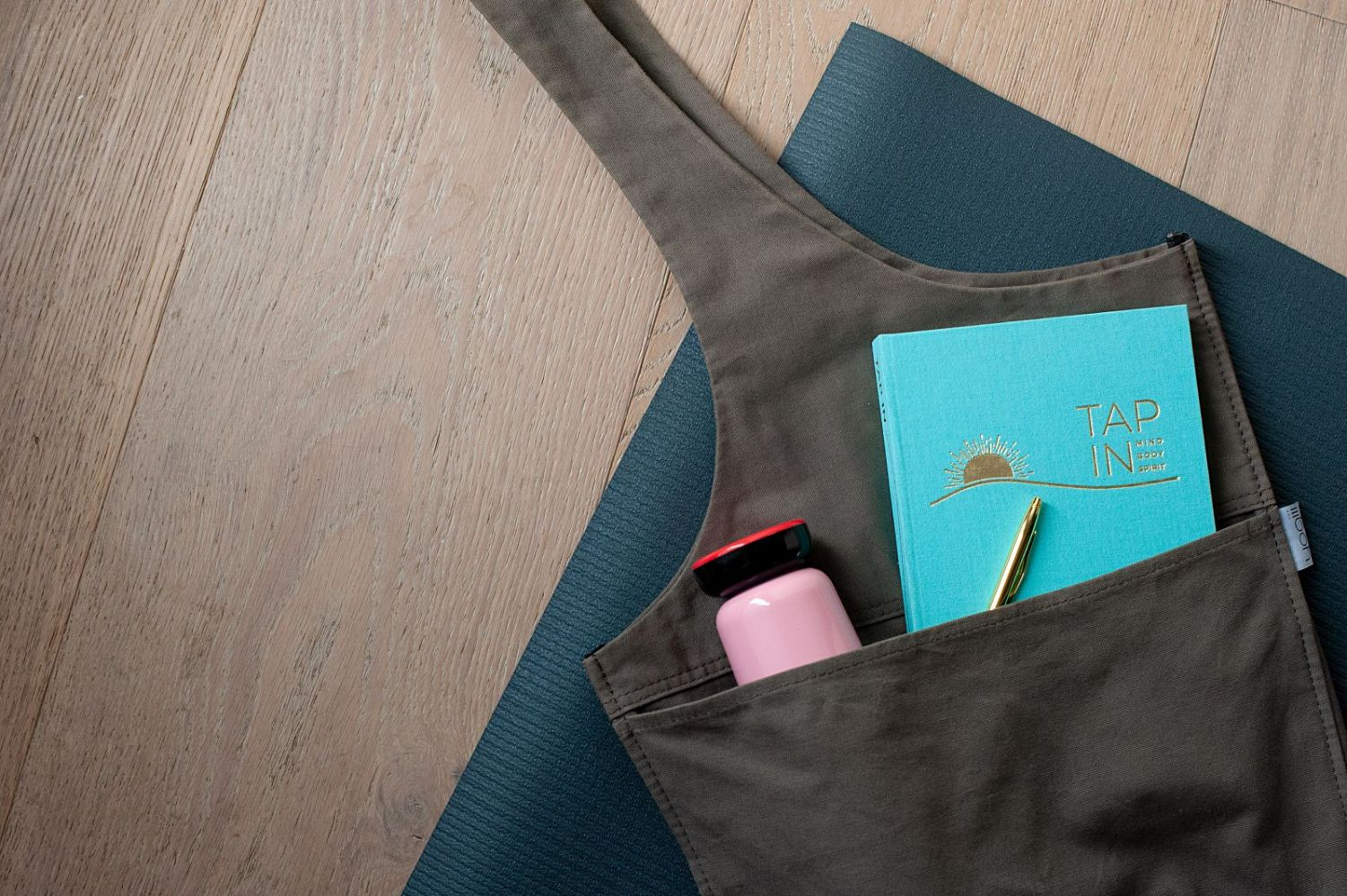 TAP IN wellness journal on a yoga mat with a water bottle.