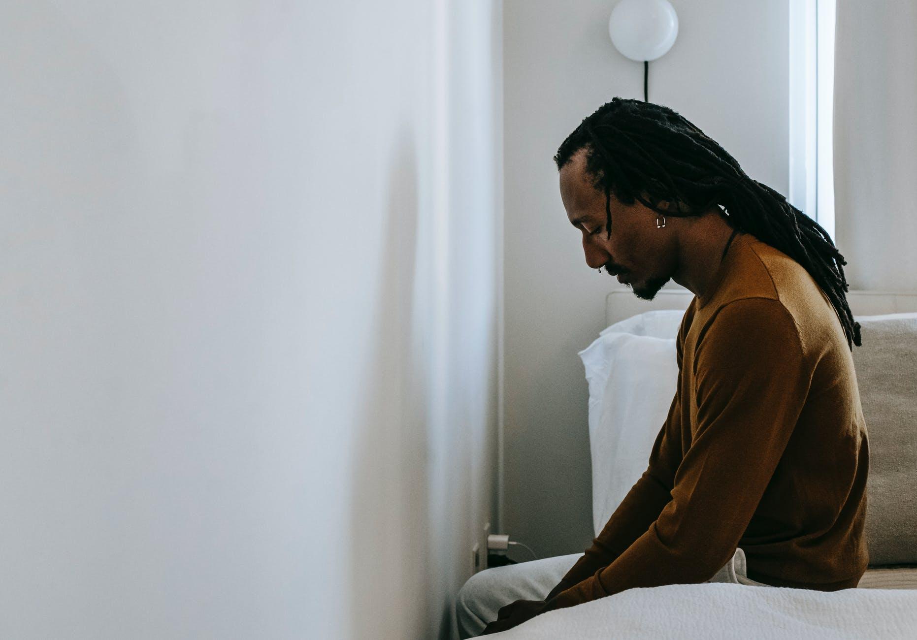depressed black man on bed at home