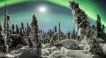 A panoromic stitch capturing a winter landscape, the aurora borealis, and the moon in Fairbanks, Alaska