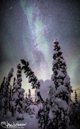 Traces of the aurora borealis flow through the bright band of the Milky Way in Fairbanks, Alaska.
