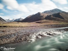 A glacial stream flows out of the mountains near Atigun Pass, Brooks Range, Alaska