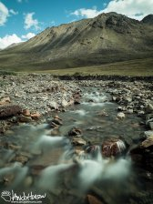 A crystal clear stream flows from the mountains north of Atigun Pass, Brooks Range, Alaska.