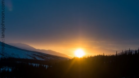 After an afternoon of lightly blowing snow, the sun broke through the clouds and burned an orange hole through the sky just south of the Coldfoot, AK