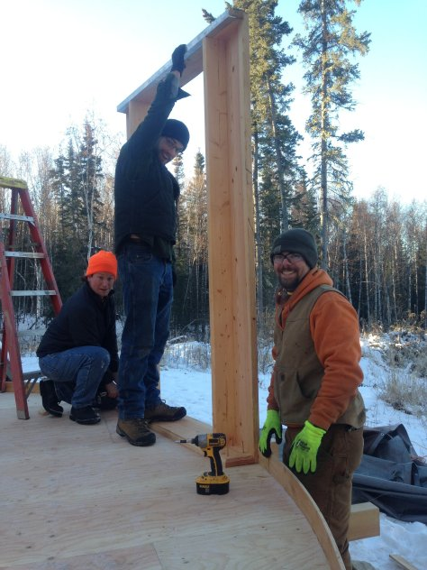 The yurt had windows and doors framed first. The tops of the framing lined up with the lathe walls and a cable was strung in a circle around the top. That cable supported the roof rafter boards and vinyl.