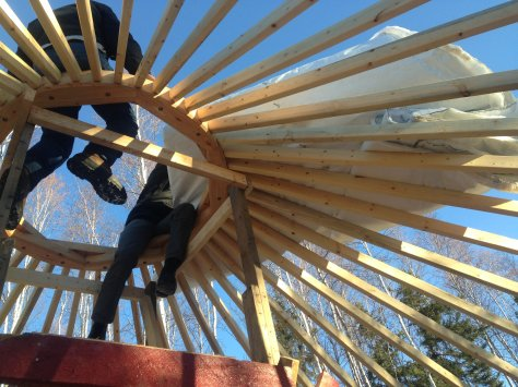 The center ring is supported by a rafter boards joined to the circular cable running around the outside. It's amazing to support a roof without a sing nail!