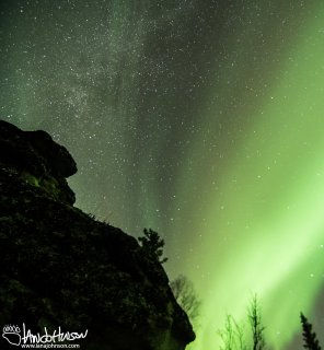 The Aurora and Milky way melt together over angel rocks.