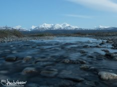 A shallow melt water stream pours of round boulders and rocks.
