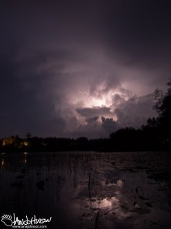 A twisting lightening bolt flashes high in the sky and bounces off the still lake