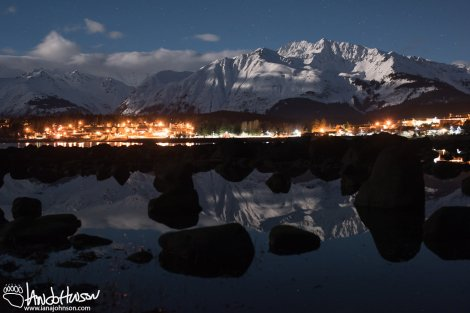 The city of Haines and the mountains behind it reflect in an inter-tidal pool.