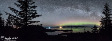 The Milky Way and Aurora stretch over Port Frederick in Hoonah, Alaska