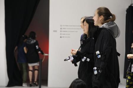 Visitors wearing a garment with Vibropixels attached view themselves in a mirror.