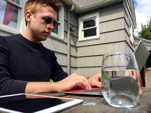 Ian L Hayes, seated outside and typing on a MacBook Air with an iPad for reference and a glass of water nearby.