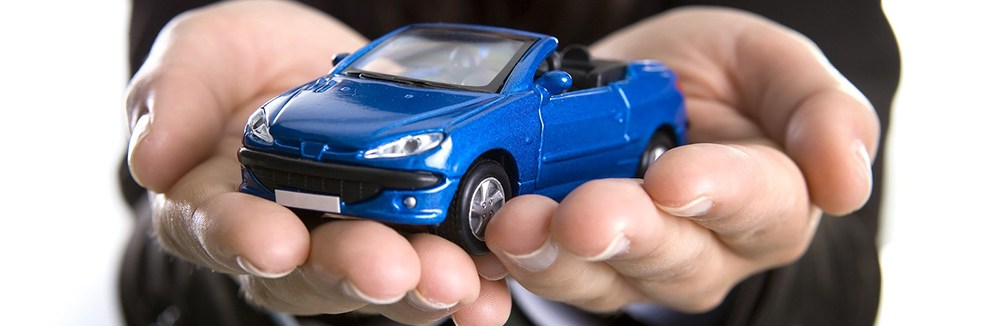 Toy car being held in the hands of an insurance agent