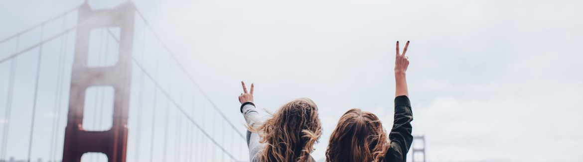 Two girls throwing peace signs by the Golden Gate Bridge.