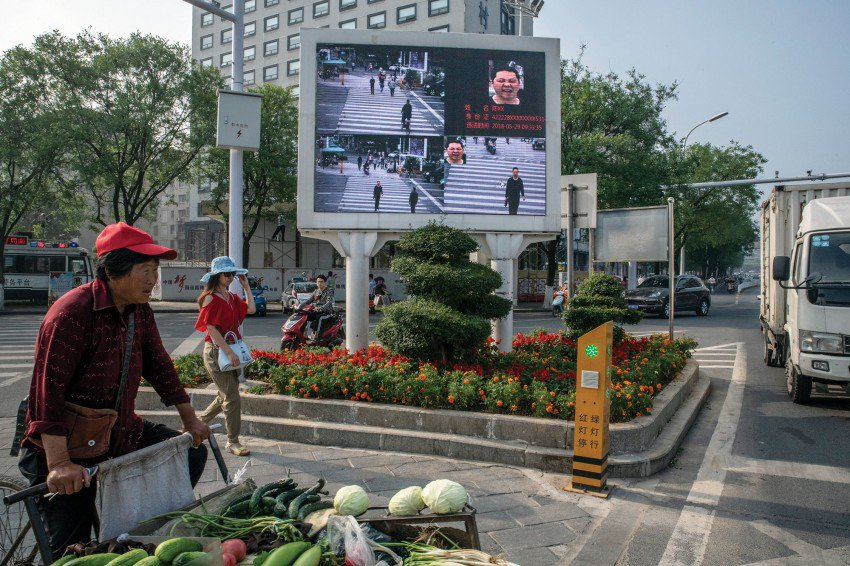 In the city of Xiangyang, cameras linked to face-recognition technology project photos of jaywalkers, with names and ID numbers, on a billboard.